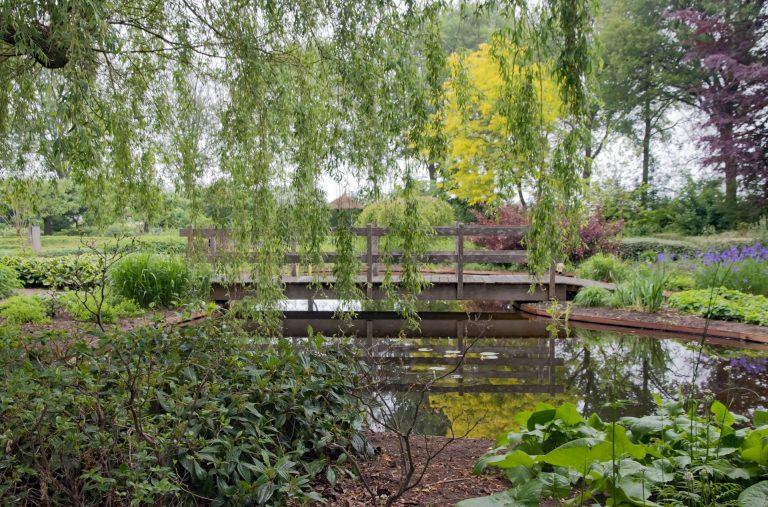 vlonderbrug in ene prachtige landelijke tuin met vijver
